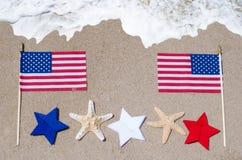 Drapeau américain avec des étoiles de mer sur la plage sablonneuse Images stock