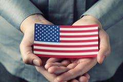 Drapeau américain dans des paumes Photographie stock libre de droits