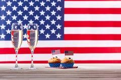 Drapeau américain, deux verres de champagne et petits gâteaux Photo libre de droits