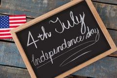 Drapeau américain et ardoise avec texte le Jour de la Déclaration d'Indépendance du 4 juillet Photographie stock