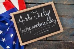 Drapeau américain et ardoise avec texte le Jour de la Déclaration d'Indépendance du 4 juillet Photos stock