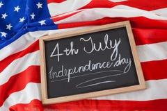 Drapeau américain et ardoise avec texte le Jour de la Déclaration d'Indépendance du 4 juillet Photos libres de droits