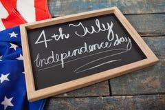 Drapeau américain et ardoise avec texte le Jour de la Déclaration d'Indépendance du 4 juillet Photo stock
