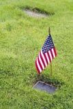 Drapeau américain et fleurs sur le Graveside de vétéran Images libres de droits