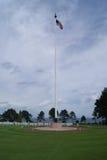 Drapeau américain ondulant à un cimetière de guerre de la Normandie Photographie stock