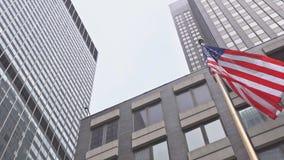 Drapeau américain ondulant contre deux gratte-ciel et un ciel bleu banque de vidéos