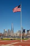 Drapeau américain se tenant grand en Liberty State Park, NJ, avec la vue de l'architecture moderne de Manhattan, NY photographie stock