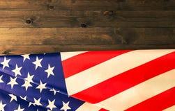 Drapeau américain se trouvant sur le fond en bois foncé Photographie stock libre de droits