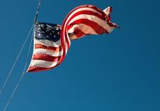 Drapeau américain soufflant dans le vent sur le ciel bleu Photo stock