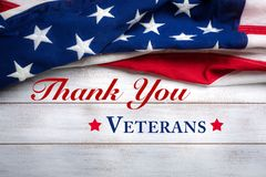 Drapeau américain sur un fond en bois porté blanc avec la salutation de jour du ` s de vétéran images stock