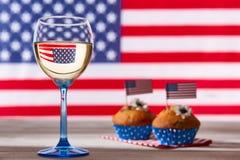 Drapeau américain, verre de vin blanc et petits gâteaux Images stock