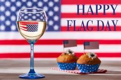 Drapeau américain, verre de vin blanc et petits gâteaux mignons Photographie stock libre de droits