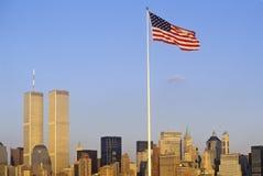Drapeau américain volant au-dessus de l'horizon de New York City du port de New York, NY Image libre de droits