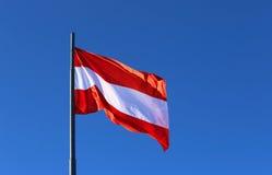Drapeau autrichien ondulant dans le ciel sans nuages bleu Photo stock