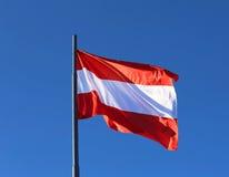Drapeau autrichien ondulant dans le ciel sans nuages bleu Photographie stock libre de droits