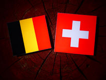 Drapeau belge avec le drapeau suisse sur un tronçon d'arbre d'isolement photos libres de droits