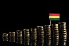 Drapeau bolivien avec le sort de pièces de monnaie d'isolement sur le noir Photo stock