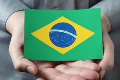 Drapeau brésilien dans des paumes Photographie stock libre de droits