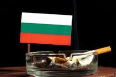 Drapeau bulgare avec la cigarette brûlante dans le cendrier d'isolement sur le noir Photo libre de droits