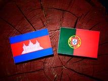 Drapeau cambodgien avec le drapeau portugais sur un tronçon d'arbre d'isolement Images stock