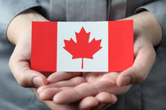 Drapeau canadien dans des paumes Images libres de droits