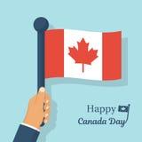 Drapeau canadien se tenant dans des mains Image libre de droits