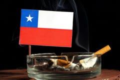 Drapeau chilien avec la cigarette brûlante dans le cendrier d'isolement sur le noir Images libres de droits