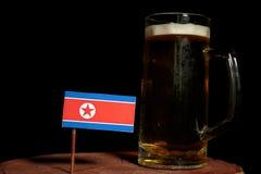 Drapeau coréen du nord avec la tasse de bière sur le noir images stock