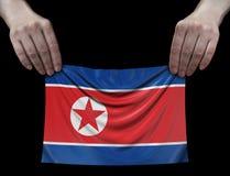 Drapeau coréen du nord dans des mains images stock