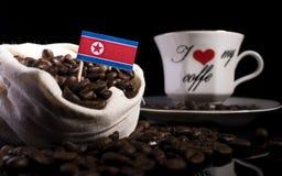 Drapeau coréen du nord dans un sac avec des grains de café sur le noir Image libre de droits
