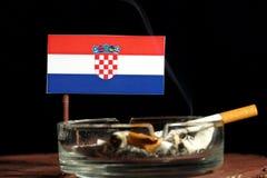Drapeau croate avec la cigarette brûlante dans le cendrier sur le noir Photo stock