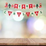 Drapeau d'étamine de Joyeux Noël au-dessus de table et de fest en bois vides de tache floue Photographie stock libre de droits