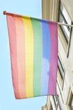 Drapeau d'arc-en-ciel accrochant sur un bâtiment Images libres de droits