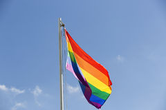 Drapeau d'arc-en-ciel sur un mât de drapeau Photo stock