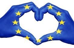 Drapeau d'Union européenne peint sur des mains formant un coeur d'isolement sur le fond blanc, concept de l'Europe Photographie stock