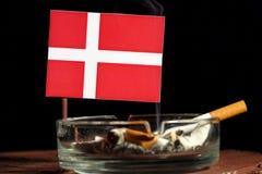 Drapeau danois avec la cigarette brûlante dans le cendrier d'isolement sur le noir Photographie stock