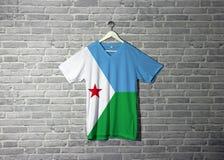 Drapeau de Djibouti sur la chemise et accrocher sur le mur avec le papier peint de modèle de brique photographie stock libre de droits