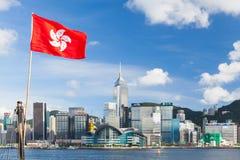 Drapeau de Hong Kong ondulant au-dessus du ciel bleu dans la ville Photo stock