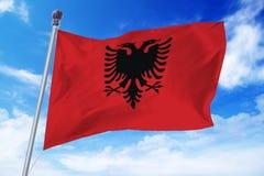 Drapeau de l'Albanie se développant contre un ciel bleu clair Photographie stock libre de droits
