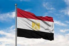 Drapeau de l'Egypte ondulant dans le vent contre le ciel bleu nuageux blanc Indicateur ?gyptien photographie stock