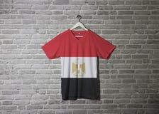 Drapeau de l'Egypte sur la chemise et accrocher sur le mur avec le papier peint de modèle de brique image libre de droits