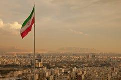 Drapeau de l'Iran dans le vent au-dessus de l'horizon de Téhéran Photographie stock