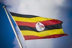 Drapeau de l'Ouganda dans le vol dessus en soleil en Afrique Photo libre de droits
