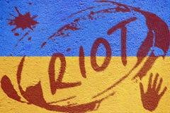 Drapeau de l'Ukraine peint sur le vieux mur en béton avec l'inscription d'ÉMEUTE Photos libres de droits