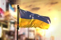 Drapeau de l'Ukraine sur le fond brouillé par ville au lever de soleil Backligh image stock