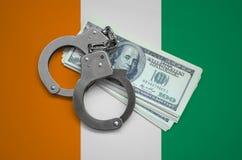 Drapeau de la Côte d'Ivoire avec des menottes et un paquet de dollars Corruption de devise dans le pays crimes financiers photos stock