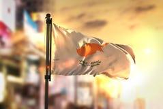 Drapeau de la Chypre sur le fond brouillé par ville au contre-jour de lever de soleil images stock