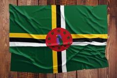 Drapeau de la Dominique sur un fond en bois de table Vue sup?rieure froiss?e de drapeau dominicain image libre de droits