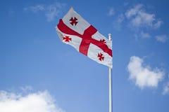 Drapeau de la Géorgie au-dessus d'un ciel bleu nuageux Image libre de droits