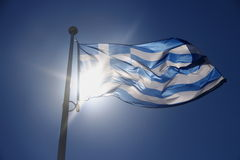 Drapeau de la Grèce sur le ciel bleu, sujet éclairé à contre-jour Image stock